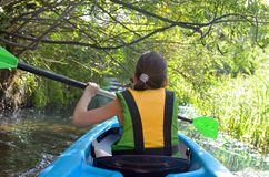 Family kayaking, child paddling in kayak on river canoe tour, kid on active autumn weekend and vacation, sport and fitness. Concept stock photography