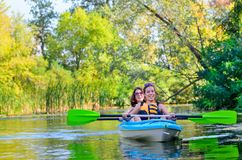 Family kayaking, mother and child paddling in kayak on river canoe tour, active autumn weekend and vacation, sport and fitness. Concept Stock Images