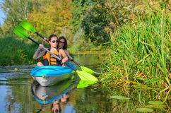 Family kayaking, mother and child paddling in kayak on river canoe tour, active autumn weekend and vacation, sport and fitness. Concept Stock Photography