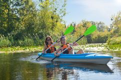 Family kayaking, mother and child paddling in kayak on river canoe tour, active autumn weekend and vacation, sport and fitness. Concept Royalty Free Stock Photo