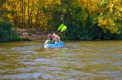 Family kayaking, mother and child paddling in kayak on river canoe tour, active summer weekend and vacation. Sport and fitness concept Royalty Free Stock Image