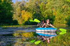 Family kayaking, mother and child paddling in kayak on river canoe tour, active summer weekend and vacation. Sport and fitness concept Stock Images