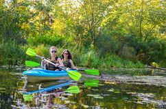 Family kayaking, mother and child paddling in kayak on river canoe tour, active summer weekend and vacation. Sport and fitness concept Royalty Free Stock Images