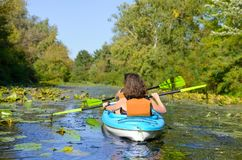Family kayaking, mother and child paddling in kayak on river canoe tour having fun, active weekend and vacation, fitness co. Family kayaking, mother and child Royalty Free Stock Images