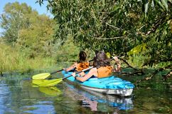 Family kayaking, mother and child paddling in kayak on river canoe tour having fun, active weekend and vacation, fitness co. Family kayaking, mother and child Stock Photos
