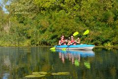 Family kayaking, mother and daughter paddling in kayak on river canoe tour having fun, active autumn weekend with children stock photography