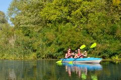 Family kayaking, mother and daughter paddling in kayak on river canoe tour having fun, active autumn weekend with children royalty free stock image