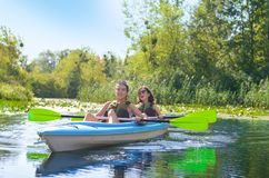 Family kayaking, mother and daughter paddling in kayak on river canoe tour having fun, active autumn weekend Royalty Free Stock Photography