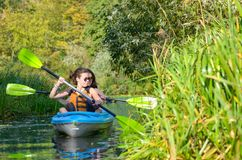 Family kayaking, mother and daughter paddling in kayak on river canoe tour having fun, active autumn weekend Royalty Free Stock Image