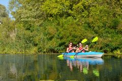 Family kayaking, mother and daughter paddling in kayak on river canoe tour having fun, active autumn weekend. And vacation with children, fitness concept Stock Photos