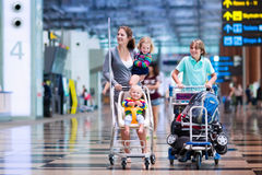 Family with kids at airport. Family traveling with kids. Parents with children at international airport with luggage in a cart. Mother holding baby, toddler girl Stock Image