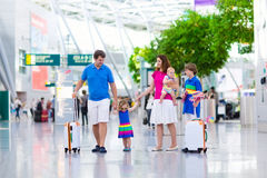 Family with kids at airport. Family traveling with kids. Parents with children at international airport with luggage. Mother and father hold baby, toddler girl Stock Images