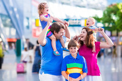 Family with kids at airport. Family traveling with kids. Parents with children at international airport with luggage. Mother and father hold baby, toddler girl Stock Image