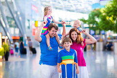 Family with kids at airport. Family traveling with kids. Parents with children at international airport with luggage. Mother and father hold baby, toddler girl Stock Photography