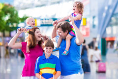 Family with kids at airport. Family traveling with kids. Parents with children at international airport with luggage. Mother and father hold baby, toddler girl Royalty Free Stock Images
