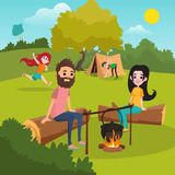Family with kids camping in park. Girl playing with kite. Boy putting up tent. Parents sitting on log near campfire Stock Photo
