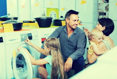 Family with kids choosing washing machine royalty free stock photography