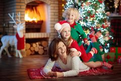 Family with kids at Christmas tree and fireplace. Royalty Free Stock Images