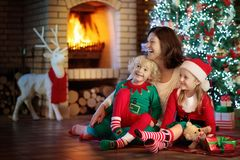 Family with kids at Christmas tree and fireplace. Royalty Free Stock Photos