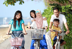 Family with kids enjoy riding bicycle outdoor in the beach Royalty Free Stock Photo