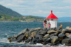 Family with kids enjoy the view to the fjord from a lighthouse at the entrance to the harbor in Drobak, Norway. Stock Images