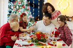 Family with kids having Christmas dinner at tree stock photos