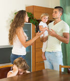Family with kids having quarrel. Angry young men with wife and two little daughters having conflict in home interior Royalty Free Stock Photography
