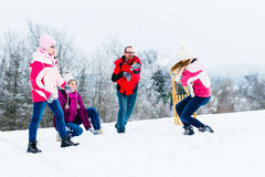 Family with kids having snowball fight in winter Royalty Free Stock Photography