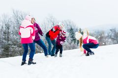 Family with kids having snowball fight in winter Stock Photography