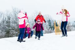 Family with kids having snowball fight in winter Royalty Free Stock Photo