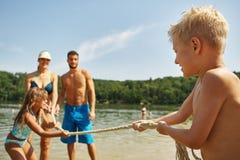 Family and kids at a lake playing tug of war Royalty Free Stock Photos