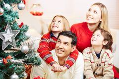 Family and kids looking at christmas tree. Family and kids looking at decorated christmas tree in the living room stock photos
