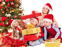 Family with kids open Christmas gift box. Happy family with children open gift box near Christmas tree. Isolated Royalty Free Stock Image