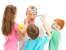 Family with kids painting with brushes on dad. Kids painting on Dad face. Isolated on white Stock Photos