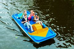 Family with kids on pedal boat stock image