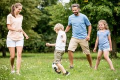 Family and kids play soccer. Together at garden in summer Stock Image