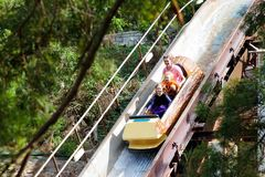 Family with kids on roller coaster in amusement theme park. Children riding high speed water slide attraction in entertainment fun. Fair during summer vacation royalty free stock photography