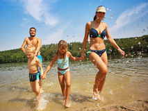 Family and kids splashing the water at the lake Royalty Free Stock Image