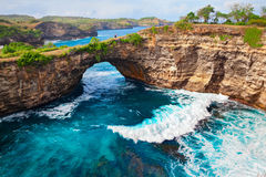 Family with kids stand on huge stone arch above sea. Family lifestyle. Father, mother with children walk and look at natural sea pool Broken Bay. Bali travel Stock Images