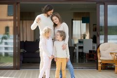 Family with kids standing outdoor holding keys of new house stock image