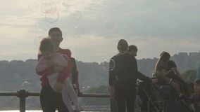 Family with kids taking walk on waterfront under soap bubbles, boy holding girl stock video footage