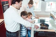 Family testing a new kitchen they intend buying in the showroom stock photography