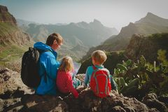 Family with kids travel hiking in mountains looking at map. Father with kids travel hiking in mountains looking at map stock photo