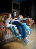 Family with kids watching TV at late evening Stock Image