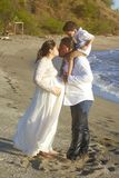 Family kiss on beach. In sunset background. Happy pregnancy theme Stock Photo