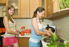 Family in the kitchen. Mother and daughter in the kitchen with some vegetables Stock Photo