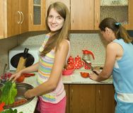 Family in the kitchen. Mother and daughter in the kitchen with some vegetables Royalty Free Stock Photos