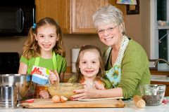 Family in kitchen. A Grandmother with two children baking cookies in the kitchen Royalty Free Stock Photo
