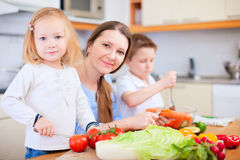 Family at kitchen. Young mother and her two kids making vegetable salad Royalty Free Stock Image