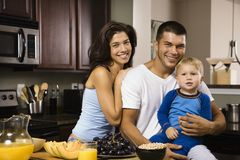 Family in kitchen. Caucasian family with toddler son in kitchen at breakfast smiling at viewer Royalty Free Stock Photos